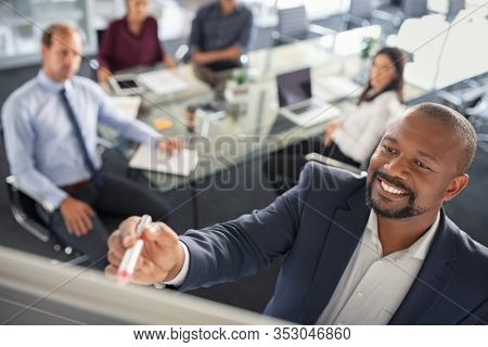 Black businessman writing on a whiteboard while explain new strategy. Mature entrepreneur discussing business ideas and plans with colleagues in background. Top view of happy african american leader i