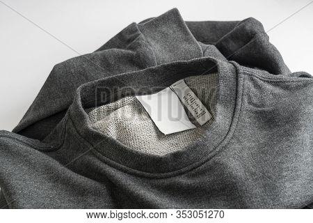 The Anti-shoplifting Label On A Gray Cotton Shirt