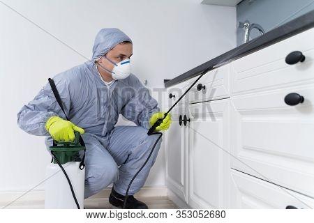 Exterminator In Workwear Spraying Pesticide With Sprayer