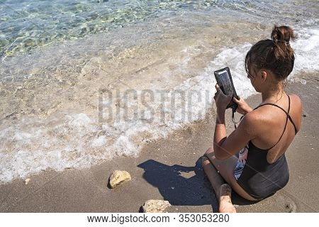 Girl With A Phone On The Seashore. A Girl Photographs Sea Waves On A Phone. Vacation, A Warm Summer