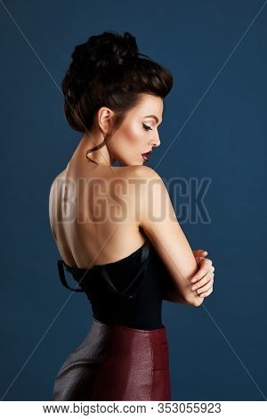 Beautiful Slim Young Brunette Woman Model Posing At The Camera On A Blue Background, Feminine Beauty