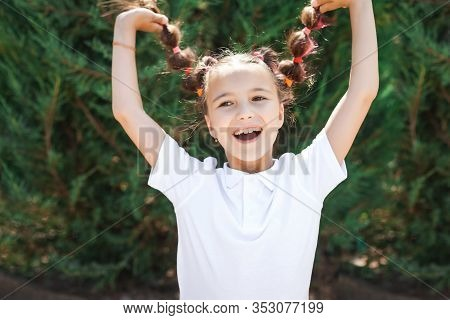 Happy Lovely Small Girl Wearing White Shirt Having Fun Holding Her Braids In A Sunny Summer Park. Pi