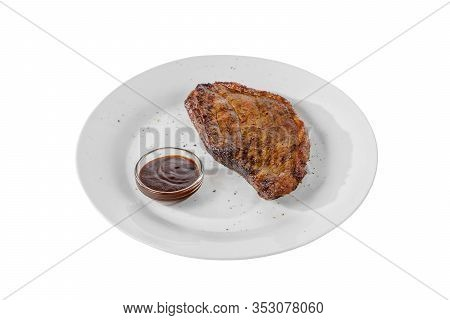 Steak Of Dark Beef, Pork, Lamb, Grilled Meat, Barbecue With Tomato, B-b-q Sauce On A Plate Isolated