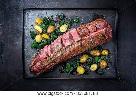 Barbecue dry aged venison tenderloin fillet steak and saddle natural with kalette and fried potatoes offered as top view on a rustic board