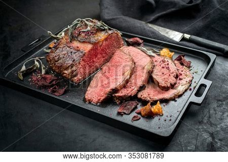 Traditional Commonwealth Sunday roast with sliced cold cuts roast beef with vegetable chips and herbs as closeup on a modern design tray