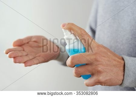 closeup of a caucasian man disinfecting his hands with blue hand sanitizer from a bottle