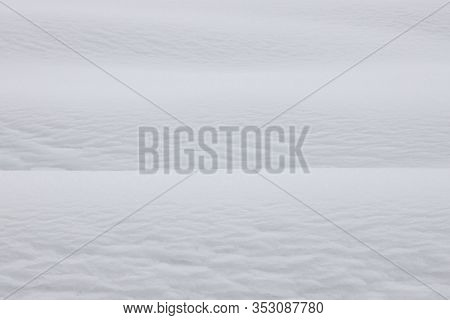 Snowy white background. The texture of the snow. Shiny snow with bokeh and blurred background close-up. White snow-covered field. Macro photo of snow.