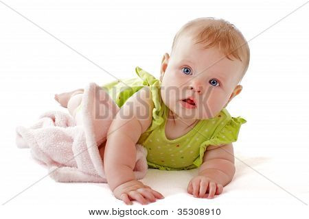 Baby With Bright Blue Eyes On Tummy With Soft Blanket.
