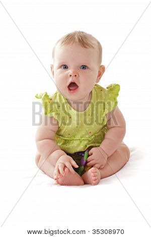 Adorable Laughing Blue Eyed Baby Sits With Her Toy Rattle.