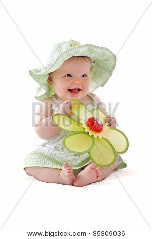 Adorable Baby Girl In Pretty Dress And Sun Hat Sits And Plays With Big Toy Flower