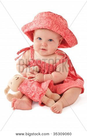 Smiling Baby Girl In Pink Dress And Sun Hat Sits And Plays With Matching Toy Rabbit