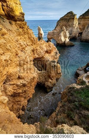 Scenic Natural Cliff Formations And Arches Of Algarve Coastline With Turquoise Water At Ponta Da Pie