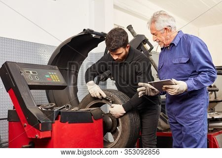 Mechatronics engineer in training with rim and tires at tire assembly next to master in auto repair shop