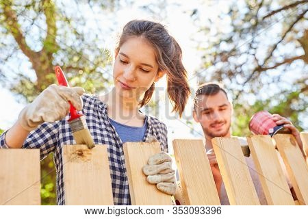 Young woman and friend together in priming and varnishing wooden fence in the garden