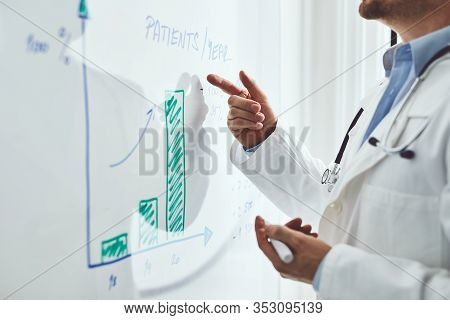 Doctor Explaining Statistics Of Disease On White Board