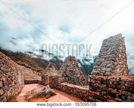 Sunshine breathtaking view of Machu Picchu stone anchient walls and temple among mountains covered with clouds