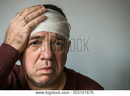 Man with concussion, head injury. His head is bandaged