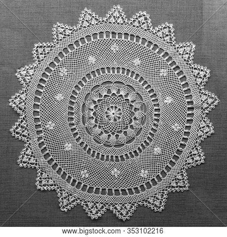 Handmade lace on black background. Macrame fabric lace doily. Crocheted white lace decorative napkin