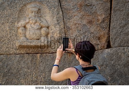 Girl Tourist Shoots A Photo On A Smartphone Of An Ancient Bas-relief . The Group Of Monuments At Ham