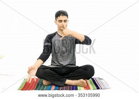 Full Body Shot Of Male Teenager Doing Nadi Shdhana Pranayama Or Alternate Nostril Breathing Isolated