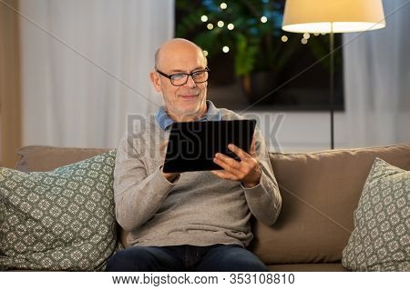 technology, old age and people concept - happy smiling bald senior man with tablet pc computer sitting on sofa at home in evening