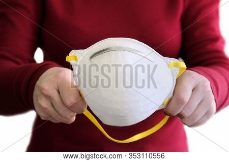 Famale Hands Holding A White Protective Mask Isolated On White.