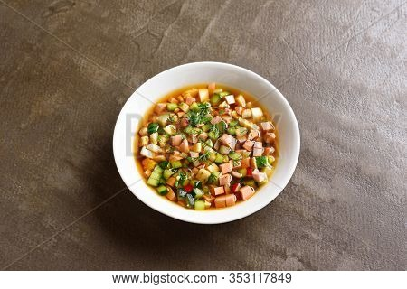 Close Up Of Cold Russian Okroshka Soup With Sausage, Vegetables And Kvass Over Brown Stone Backgroun
