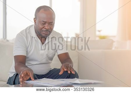 Portrait Of African Man Reads Negative Document. Bank Notice, Bankruptcy, Loss Of A Loved One. Bad U