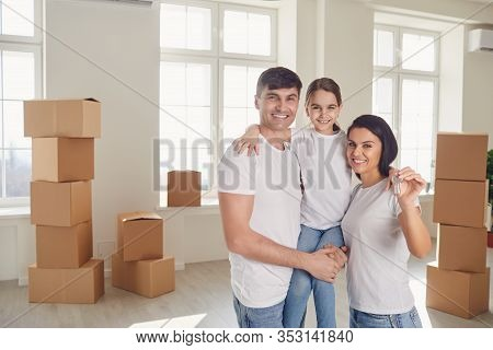 Happy Family With Keys In Their Hands Stands In A New House.