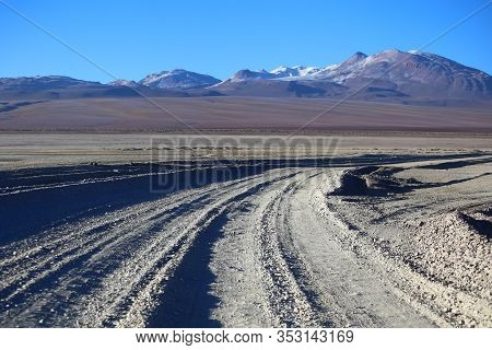 Bolivia Andes, Highland Desert. Dust Road Covered By Snow In The Morning. Arid And Mountains In The