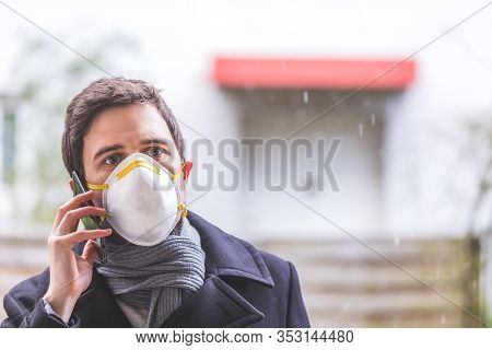 Flue And Corona Safety Concept. Business Man Wearing Face Mask To Protect Himself And Using Smartpho