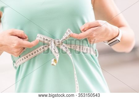 Weight Loss And Slim Body Of A Young Woman. Girl Measuring Her Waistline Body With Measure Tape.