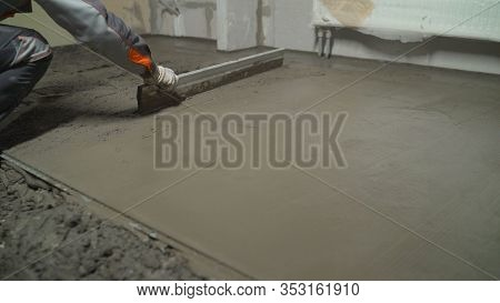 Leveling Concrete With Trowels, Laborer Spreading Poured Concrete. Indication Of Mortar On The Floor
