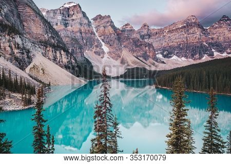 Turquoise Waters Of Moraine Lake As The Sunrises Turning The Mountains Peaks A Pink Hue. Moraine Lak