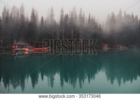 The Emerald Lake Boat House With Stacked Colorful Canoes Sits In The Thick Fog Across Emerald Water