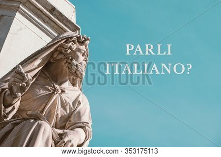 closeup of a sculpture at the base of the Column of the Immaculate Conception, at Mignanelli square in Rome, Italy, and the question parli italiano, do you speak Italian written in Italian, on the sky
