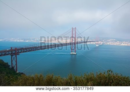 View Of 25 De Abril Bridge In Lisbon, Portugal. Ponte 25 De Abril. A Suspension Bridge Connecting Th