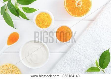 Natural Homemade Cosmetics: Scrub, Cream And Sea Salt With Orange Fruit On White Background. Organic