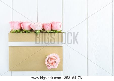 Pink Roses In Envelope With White Ribbon On White Wooden Background. Flat Lay, Top View, Copy Space.
