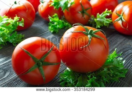 Fresh Tomatoes And Lettuce On Dark Wooden Table.