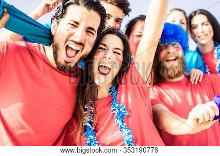 Football Fan Screaming, With Red Shirts Inside Of The Stadium . Group Of Young People Very Excited A