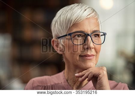 Beautiful senior business woman thinking and wearing spectacles. Thoughtful old woman teacher looking away with eyeglasses. Closeup face of mature pensive lady contemplating the future with copy space