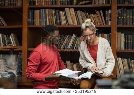 Cheerful college students studying together for next exam. Two multiethnic friends smiling and taking notes in a library. African man and young woman discussing on note for university exam.