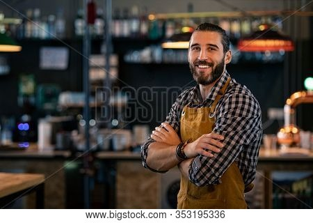 Happy satisfied bartender with apron near counter with crossed arms and looking at camera. Confident coffee shop waiter smiling at cafeteria. Successful proud young brewer at his pub with copy space.