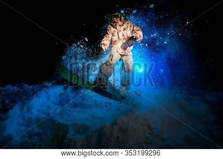 Darkened Shot Of Male Freerider Jumping On Snowboard
