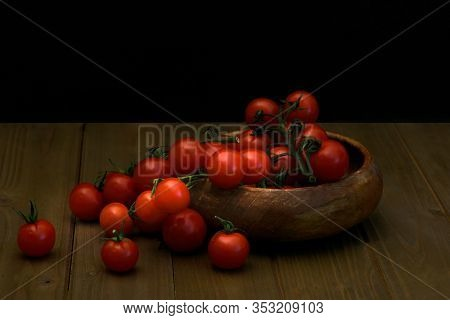 Fresh Cherry Tomatoes On Black Background Viewed From The Side, Fresh Whole And Cut (halved) Red Tom