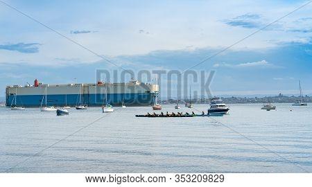 Tauranga, New Zealand - February 21 2020; Waka Ama Paddlers Head Across Bay With Large Vehicle Carri