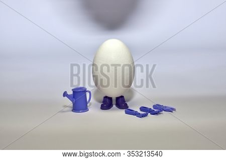 White Egg In Shoes Stands In The Middle With A Mini Inventory With Plants, A Spatula, A Rake, A Seca