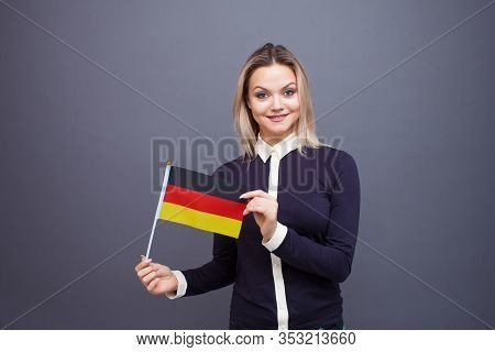 Immigration And The Study Of Foreign Languages, Concept. A Young Smiling Woman With A Germany Flag I