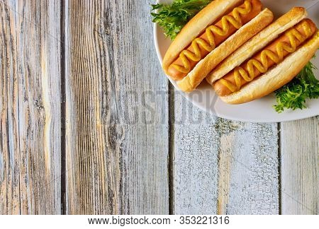 Hot Dog With Mustard On White Plate On Wooden Background.